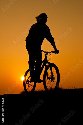 silhouet of a young adult riding a bike