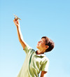 Young boy playing with an airplane with the blue sky as the back