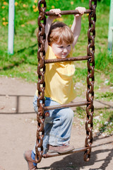 A little girl trying to climb a rope-ladder