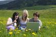 Jugendliche mit Laptop in freier Natur