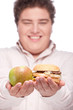 apple and hamburger in hands of a young chubby man, isolated