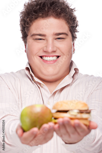 Young chubby man holding apple and hamburger, isolated on white