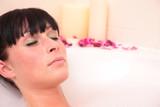 woman lying in tub relaxing in a lot of foam poster