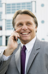 Happy businessman chatting on cellphone.