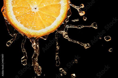 Fresh orange into water with a splash