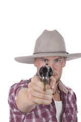 young cowboy with pistol pointed directly at camera