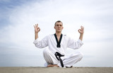 Martial art master  meditate, sitting at sand over sky