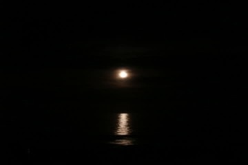 dark moonrise over the ocean