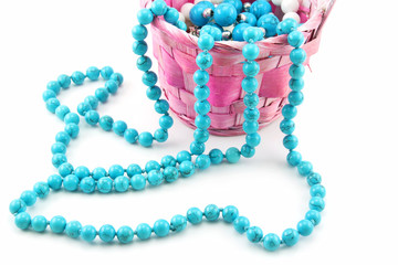 Colored Pearl Beads in Pink Wicker Basket Isolated