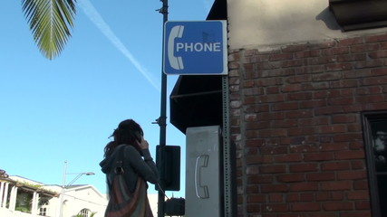 Woman talks on a pay phone - HD
