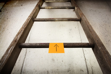 Old wooden ladder on a cement wall
