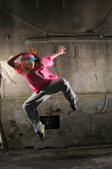 Urban dancer jumping on dark street against old grungy wall