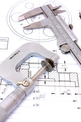 Caliper and Micrometer on blueprint vertical. Shallow dof