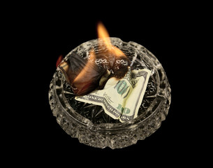 Burning dollars in ashtray isolated on black background