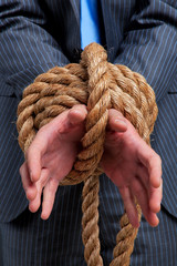 Businessman hands tied up with rope
