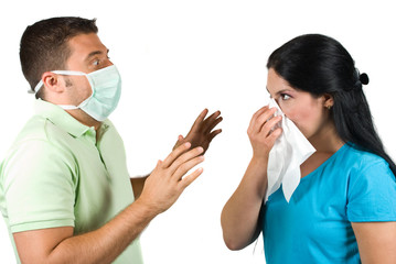Terrified man with protective mask try to stop a sneezing woman