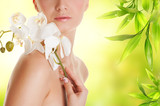 Fototapety Beautiful young woman with white orchid flower
