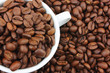 White cup with coffee beans on background