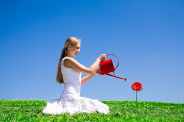 Woman watering red daisy