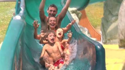 Famiglia si diverte con lo scivolo in piscina
