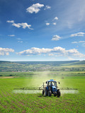 Fototapety Farming tractor plowing and spraying on field vertical
