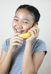 Pretty girl holding banana as a phone.