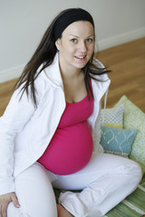 A young happy pregnant woman sitting on mat and relaxing.