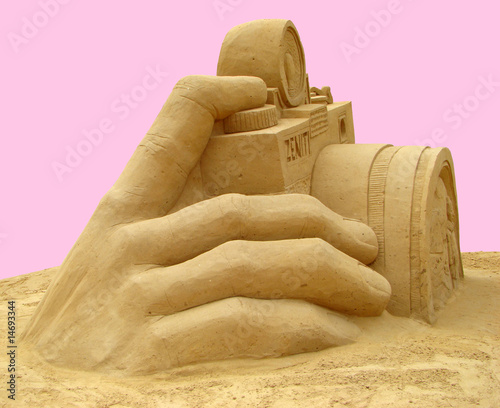 hand of man with a camera. Sculpture from sand