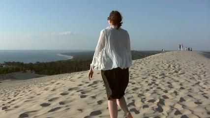 femme s'éloignat sereinement sur la dune