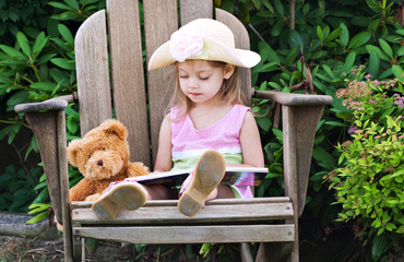 Beautiful little girl pretending to read to her teddy bear