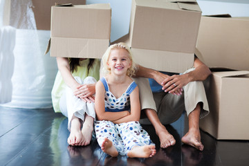 Parents and daughter playing at home with boxes