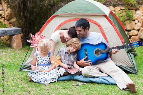 Parents and children playing a guitar in a tent