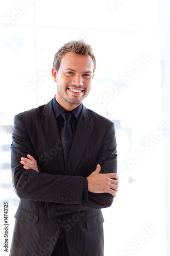 Handsome smiling businessman with folded arms
