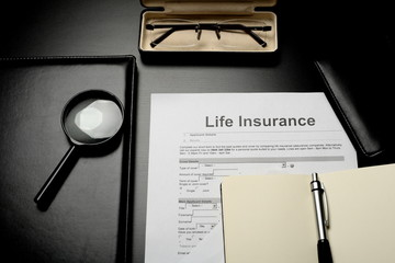 Notepads, glasses and life insurance papers