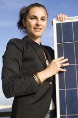 Young woman close to a solar panel