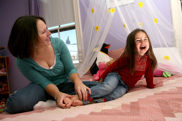 mother tickling her little girl's bare feet on the bed
