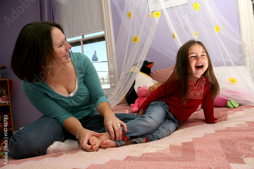 Photo: mother tickling her little girl's bare feet on the bed