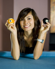 beautiful asian girl showing an eight and nine ball