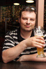 The man resting with beer in a bar
