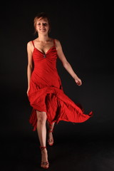 Young woman in red dress over black background
