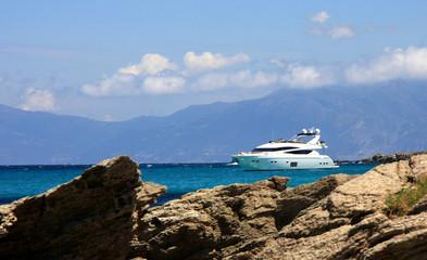 yacht behind rocks