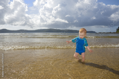 Toddler playing at beach in sunlight with impending storm