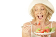 Blonde woman eating vegetable salad