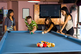 a caucasian man teaching pool to asian women