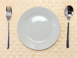 Table appointments(arrangement) of flatware on bamboo mat.