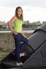 Beautiful lady smiling and standing on an old cannon