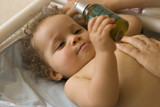 Bébé allongé tenant une huile de massage - hydratation de la pea poster