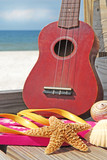 Ukulele and beach items at seashore poster