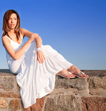 Beautiful Brunet Sitting on Top of a Stone Wall poster