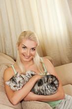 Młoda kobieta z kotów stitting na kanapie